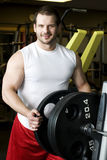 Young man putting weights on bar Stock Photos