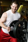Young man putting weights on bar Royalty Free Stock Images