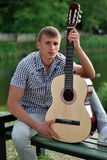 Young man with a quitar by the river. Serious young man holding a guitar by the river stock photo