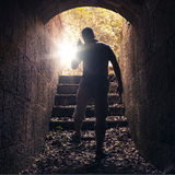 Young man with radio goes out of dark stone tunnel Royalty Free Stock Photos