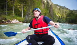 Young man in a raft boat,  paddling, smili Stock Images