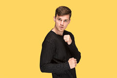 The young man with a raised fist. S on yellow studio background Royalty Free Stock Photos