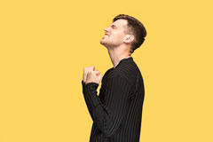 The young man with a raised fist. S on yellow studio background Royalty Free Stock Image
