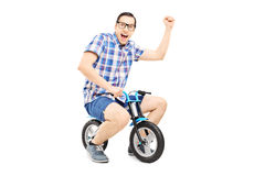 Young man with raised fist riding a small bike Royalty Free Stock Photo