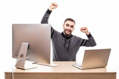 Young man with raised fists using laptop and personal computer at isolated table on white background Royalty Free Stock Photos