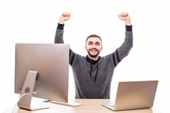 Young man with raised fists using laptop and personal computer at isolated table on white background Stock Image