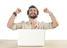 Young man with raised fists using laptop Stock Photography