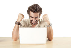 Young man with raised fists using laptop Stock Photo