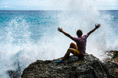 Young man with raised hands sitting on the rock with the sea waves Stock Image