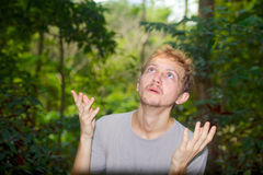 Young man raised his hands to the sky and asks. Young man threw his hands to the sky and asks sitting in a forest stock images