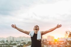 Young man raising hands over sunset sky after training Royalty Free Stock Photos