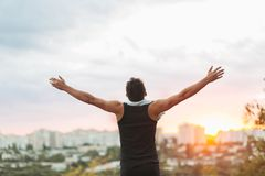 Young man raising hands over sunset sky after training Stock Images