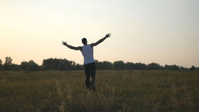 Young man with raising hands running in field and enjoying freedom. Carefree guy running on grass field at summertime