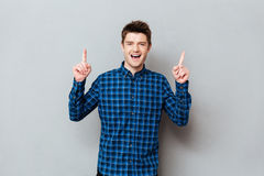 Young man raising his fingers up. Young cheerful man raising his fingers up over grey background stock photos