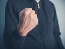 Young man raising his fist. Close up on a young man raising his fist Royalty Free Stock Image