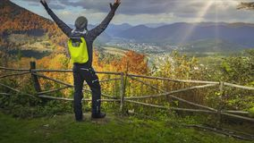 Young man raising his hands on mountain view point stock footage