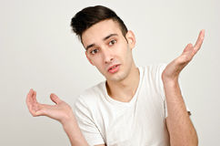 Young man raising his hands wondering... Stock Photography
