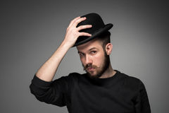 Young man raising his hat  in respect and. Young man with a mustache and beard raising his hat  in respect and admiration for someone. portrait on gray Royalty Free Stock Image