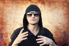 Young man rapper. On grunge background Stock Photos