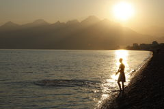 Young man in rays of sun going to swim. Young swimmer in rays of the setting sun ready to enter the water, Mediterranean Sea, Konyaalti beach, Antalya, Turkey Royalty Free Stock Image