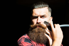 Young man with razor. Young man hipster with handsome bearded face holding cut throat razor near long fashion beard and moustache on black background studio royalty free stock photo