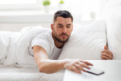 Young man reaching for smartphone in bed Stock Photo