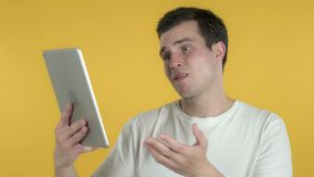 Young Man Reacting to Loss on Tablet Isolated on Yellow Background stock footage