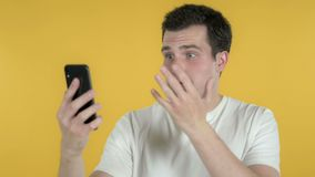 Young Man Reacting to Loss and Using Smartphone Isolated on Yellow Background stock video footage