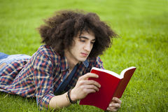 Young man read book in grass Stock Images