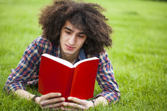 Young man read book in grass. Outdoors stock photos