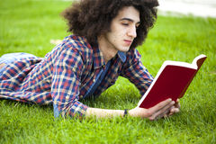Young man read book in grass Stock Photo