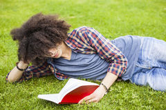 Young man read book in grass Royalty Free Stock Photography