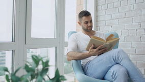 Young man read book sitting on balcony in modern apartment. Young man reading book sitting on balcony in modern apartment stock video footage