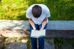 Student read a Book. Young Man read a Book in the Summer Park Royalty Free Stock Photography