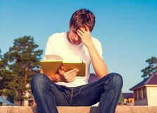 Young Man read a Book. Toned Photo of Sad Young Man read a Book outdoor Stock Images