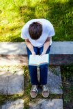 Young Man read a Book. In the Summer Park Royalty Free Stock Photo