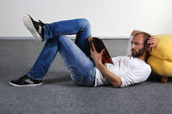 Young man read a magazine on the floor Royalty Free Stock Photos