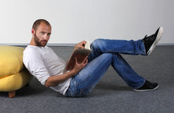 Young man read a magazine on the floor Stock Photography