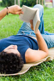 Young man reading. Young man lying on the grass and reading relaxed a book Royalty Free Stock Images