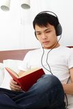 Young Man Reading. A young Asian man reading a book on a bed while listening to music on his headphones Stock Photo