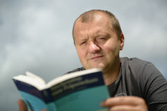 Young man reading book stock image