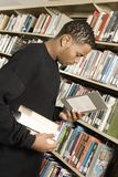 Young Man Reading Book. Young African American men reading a book at library standing by a bookshelf Royalty Free Stock Photo