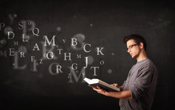 Young man reading a book with alphabet letters Royalty Free Stock Photography