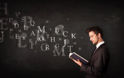 Young man reading a book with alphabet letters Stock Photography