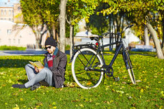 Young man reading a book in autumn park. Stock Photography
