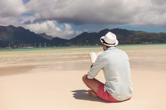 Young man reading a book on the beach Royalty Free Stock Image