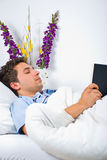 Young man reading book on bed Stock Photo