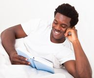 Young Man Reading Book On Bed. Happy Young African Man  Reading His Book On Bed Stock Photography