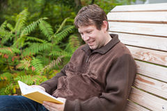 Young man reading book on bench in summer forest Stock Photo