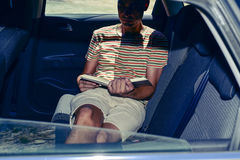 Young man reading a book in a car Stock Images
